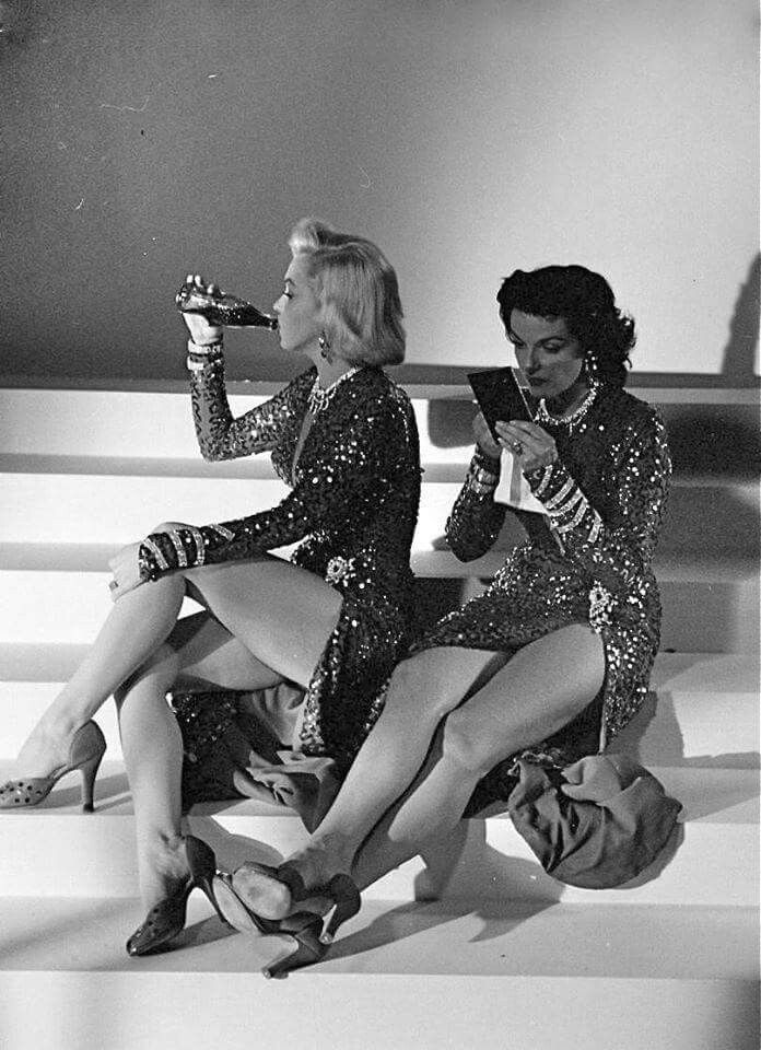 This...is...everything!!! Marilyn Monroe & Jane Russell, in matching gowns designed by Travilla, relax between photographs while they pose for publicity stills to promote their film 'Gentlemen Prefer Blondes,' Los Angeles, California, May 1953. Photo by Ed Clark. °