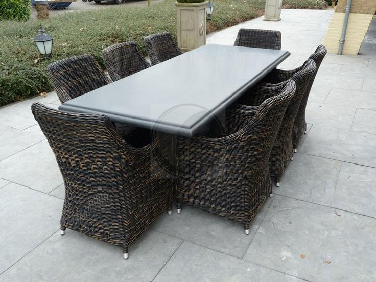 Fraai afgewerkte natuurstenen tafel met stalen frame en acht zeer robuuste vlechtwerk stoelen