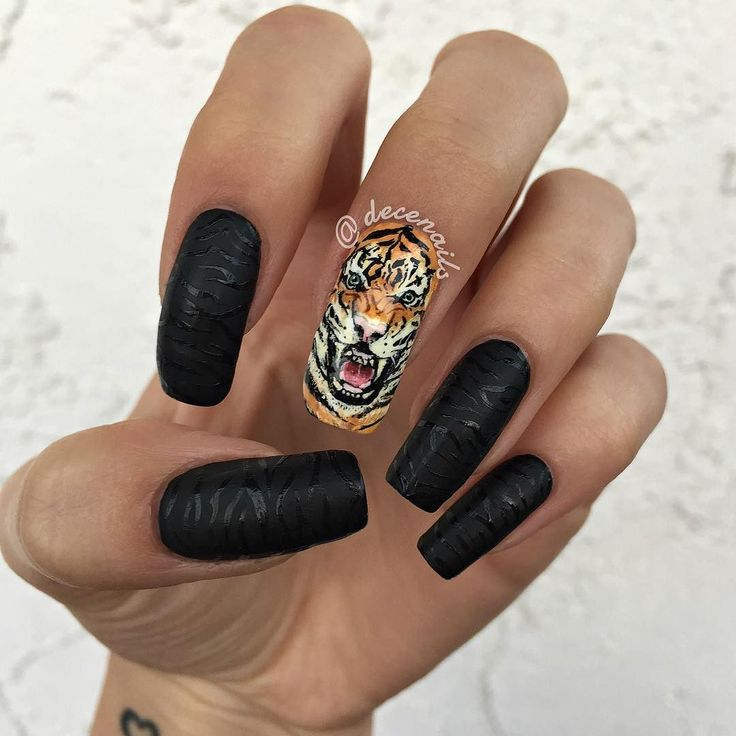 My tiger nails!   Tiger nail freehand painted with acrylic paints over OPI Alpine Snow. Matte black tiger stripe nails done with OPI Black Onyx with a Nicole by OPI Matte Top Coat (do not recommend that top coat). Stripes painted over top of the matte with black polish.   Inspired by the tiger nail by @masanong  by decenails