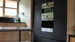 Vanluyd NV - Landelijke keuken met eik en staal - mat zwarte wand met apparaten