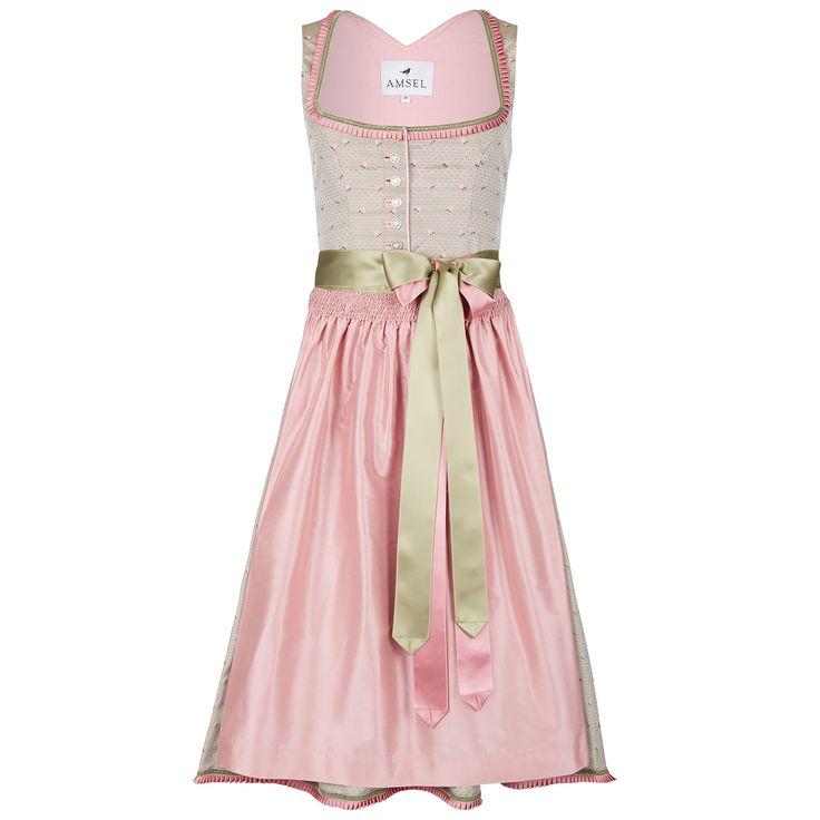Ein Zusammenspiel aus ecru und rosé. Das Kleid ist in ecru ist mit kleinen Rosen verziert. Die rosé farbene Schürze wird durch die Bändern in champagner und rosa gehalten. Samt und Rüschenborten in passender Farbe sind in Rocksaum sowie...