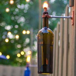 Keep bugs away with style - use a wine bottle as a citronella candle! (Photo via Design Sponge)  -I always hang wine bottles on the outside of my fence JUST IN CASE my neighbors weren't already aware of my little problem.