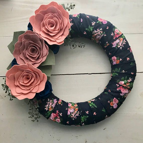 """This 14"""" straw wreath form is wrapped in a beautiful navy blue and pink floral ribbon. It is adorned in large felt flowers in shades of pink and finished with smaller blue flowers, leaves and faux greenery. This wreath will brighten your front door and welcome guests to your home"""