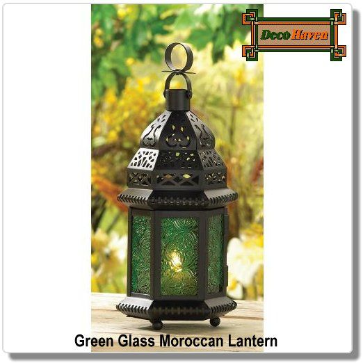 Green Glass Moroccan Lantern - A halo of emerald green casts a serene glow, as intricate cutouts cast a net of starlight into the tranquil dark. An enchanting play of shadow and motion.