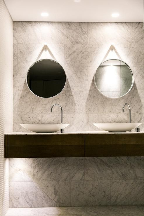 Modern master bathroom features an accent wall clad in grey marble lined with a veneer floating washstand topped with his and her bowl sinks and off-set gooseneck faucets under hanging captains' mirrors.