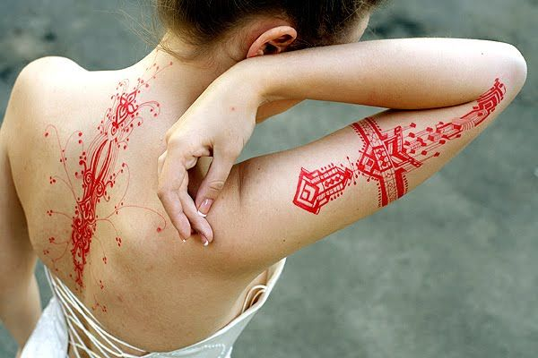 See more Red ink tattoos on back and arms