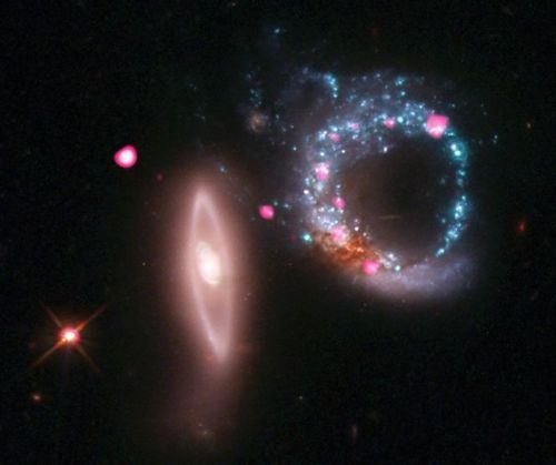 Arp 147 contains the remnant of a spiral galaxy (right) that collided with the elliptical galaxy on the left. This collision has produced an expanding wave of star formation that shows up as a blue ring containing an abundance of massive young stars. These stars race through their evolution in a few million years or less and explode as supernovas, leaving behind neutron stars and black holes.