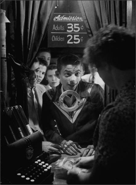 Teenage boy peering through ticket booth window at local movie theater, 1954...