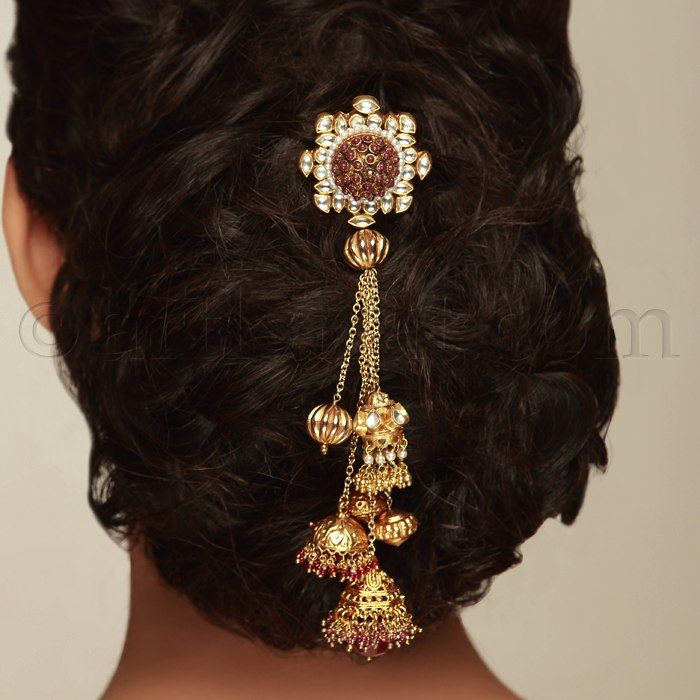 What a beautiful large low bun with juda pin! Care however should be taken before adopting such hairstyles, as due to it's high static charge, it will cause phlegm to move up in the throat, causing the voice to quaver & a frequent urge to clear the throat. A heavy chabi chhalla with a long & wide hook if inserted at the edge of the pleats of the saree, will reduce this problem as it's hook will activate the acupressure points that act to keep the throat clear.