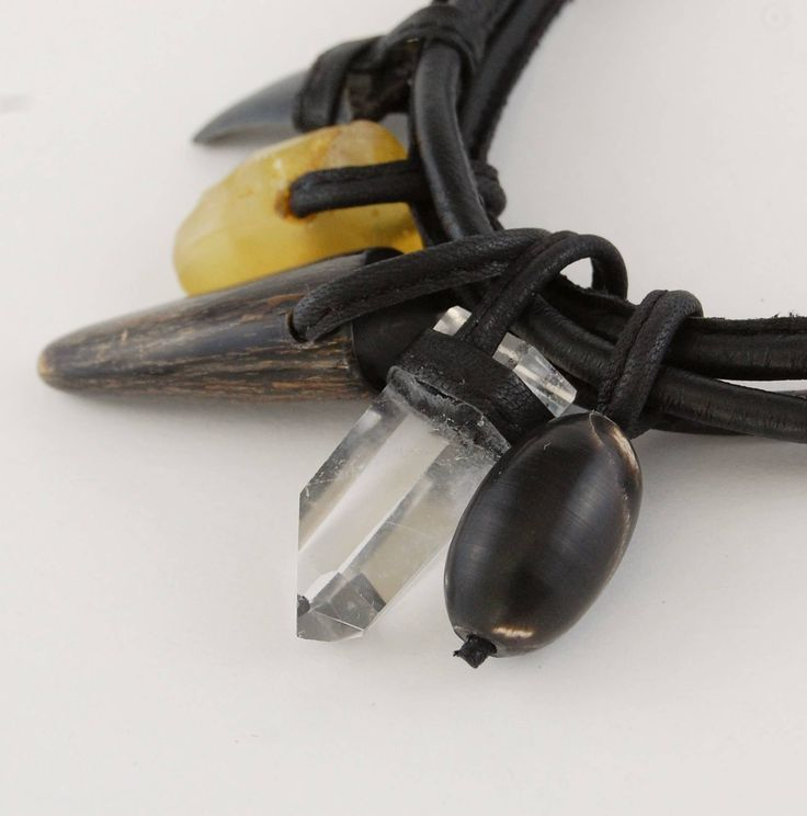 Horn tip, horn bead, natural crystal, natural amber and shark's tooth fossil on the soft leather