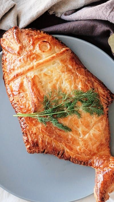 Recipe with video instructions: Elevate baked salmon with cream cheese, spinach and a warm, flaky crust shaped like a fish. Ingredients: 1 salmon fillet (sashimi grade), 2 sheets puff pastry, whole-grain mustard, 2 bunches spinach, salt, pepper, dill, (cheese sauce), 100g cream cheese, 10g mayonnaise, lemon juice, oregano, (egg wash), 1 egg, milk