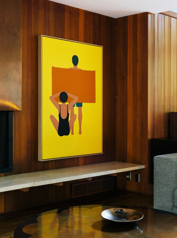 """In the living room, the painting is by Geoff McFetridge and the wood paneling is original to the house. """"Jewel-y color and simple shapes—they feel right in this house,"""" says interior designer Jessica Helgerson."""