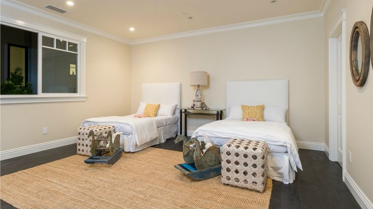 A children's room featuring the same buttery walls and ebony hardwood flooring as the previous bedroom. Recessed lighting and white crown moulding pair with vintage decorative elements to great effect. A rough textured area rug brings an additional dynamic and added interest to this already eclectic bedroom.