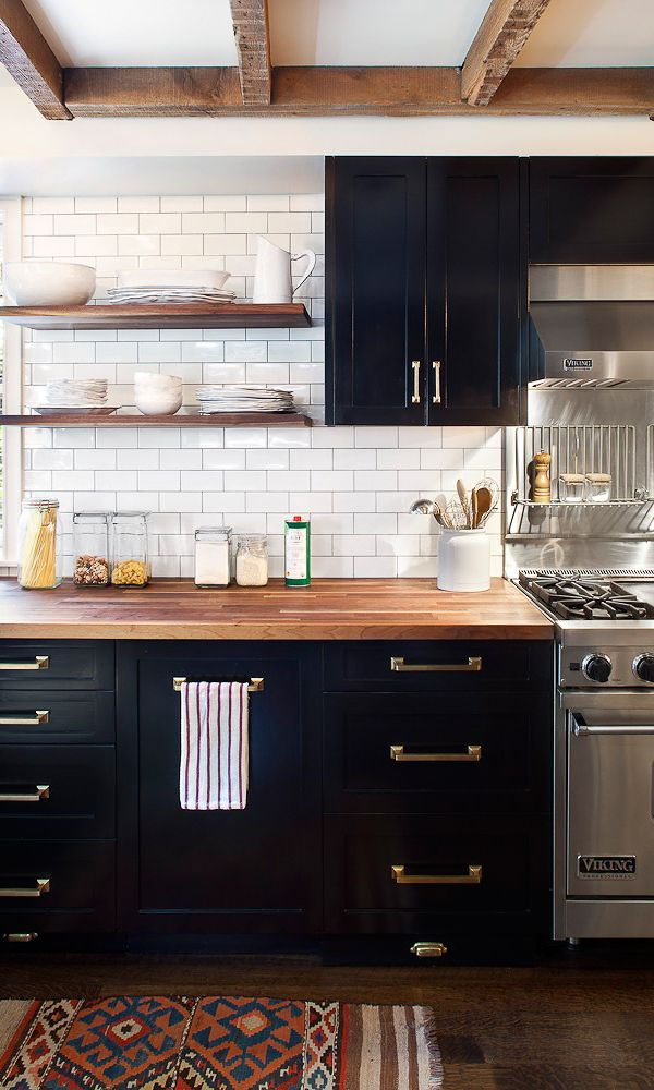 black cabinets, brass pulls, wood countertop