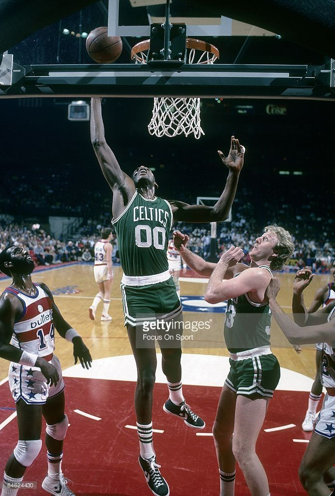 BALTIMORE, MD - CIRCA 1980's: Robert Parish #00 of the Boston Celtics goes up to grab a rebound in front of teammate Larry Bird #33 and Ricky Sobers #14 of the Washington Bullets during a mid circa 1980's NBA basketball game at the Baltimore Coliseum in Baltimore, Maryland. Parish played for the Celtics from 1980-94.