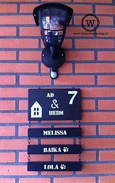 Stoer houten naambord voor bij de voordeur. Met losse naambordjes aan kettingen.