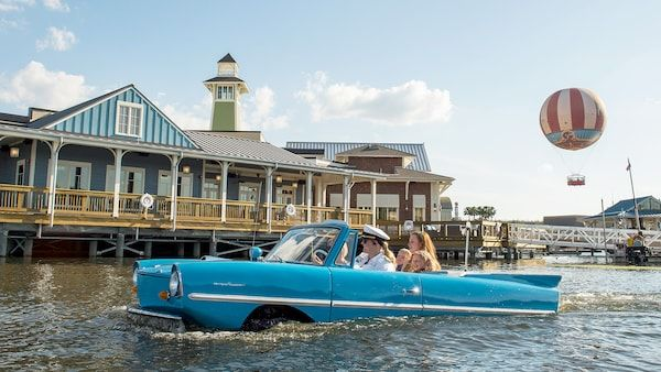 An amphibious car drives through the water with a family in the backseat with a pier behind it