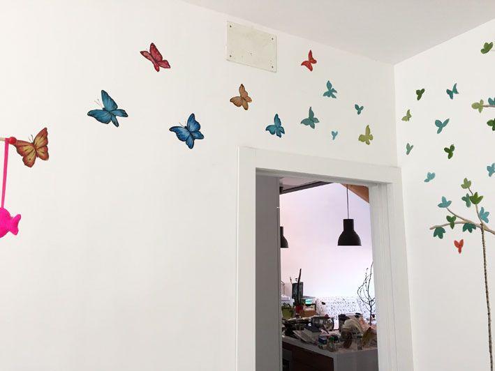 Detalle Habitación Infantil árbol. Mariposas pintadas alrededor de la paredes.
