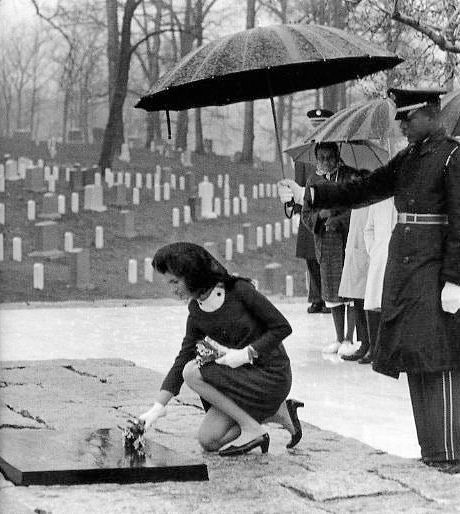Mrs. Jacqueline Kennedy places flowers on President Kennedy's grave at Arlington National Cemetery, on March 16, 1967, after a ceremony following re-interment of the body of President John F. Kennedy to the permanent grave site. (Cecil Stoughton. United States Army Signal Corps)