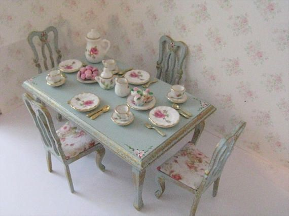 Casa de muñecas mesa y cuatro sillas, mano pintada en azul huevo de pato y adornado en oro y con la mano pintada Ramos rosa salvaje. Cada silla tiene un asiento completo soplado rosas cubren un conjunto magnífico. Este sistema se vende con el hermoso diseño rosa platos y dulces