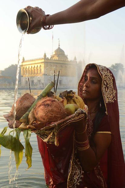 A woman holds a platter of fruit in water near the Durgiana temple in Amritsar, India pic by Narinder Nanu/AFP/Getty Images