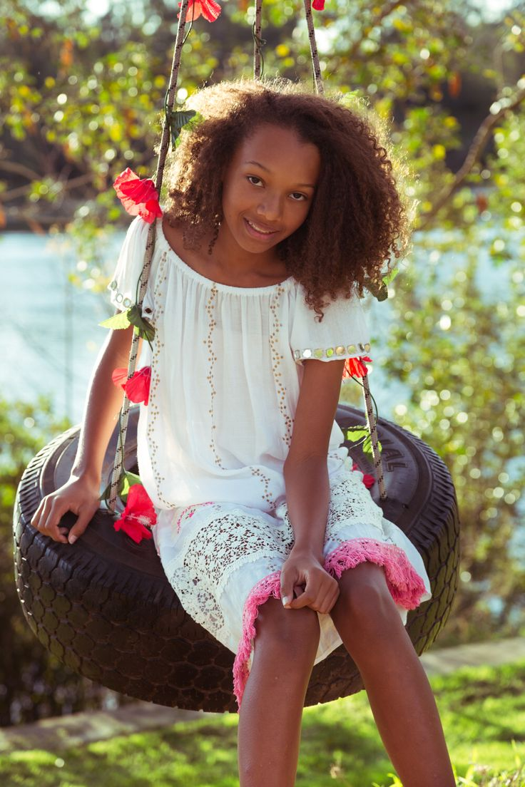 Ruby Yaya | Kids Wear. Fashion for the boho & stylish kids. Colourful, fun & comfortable dresses and Blouses.  Beatiful girl in white Ruby yaya dress in a tire swing.