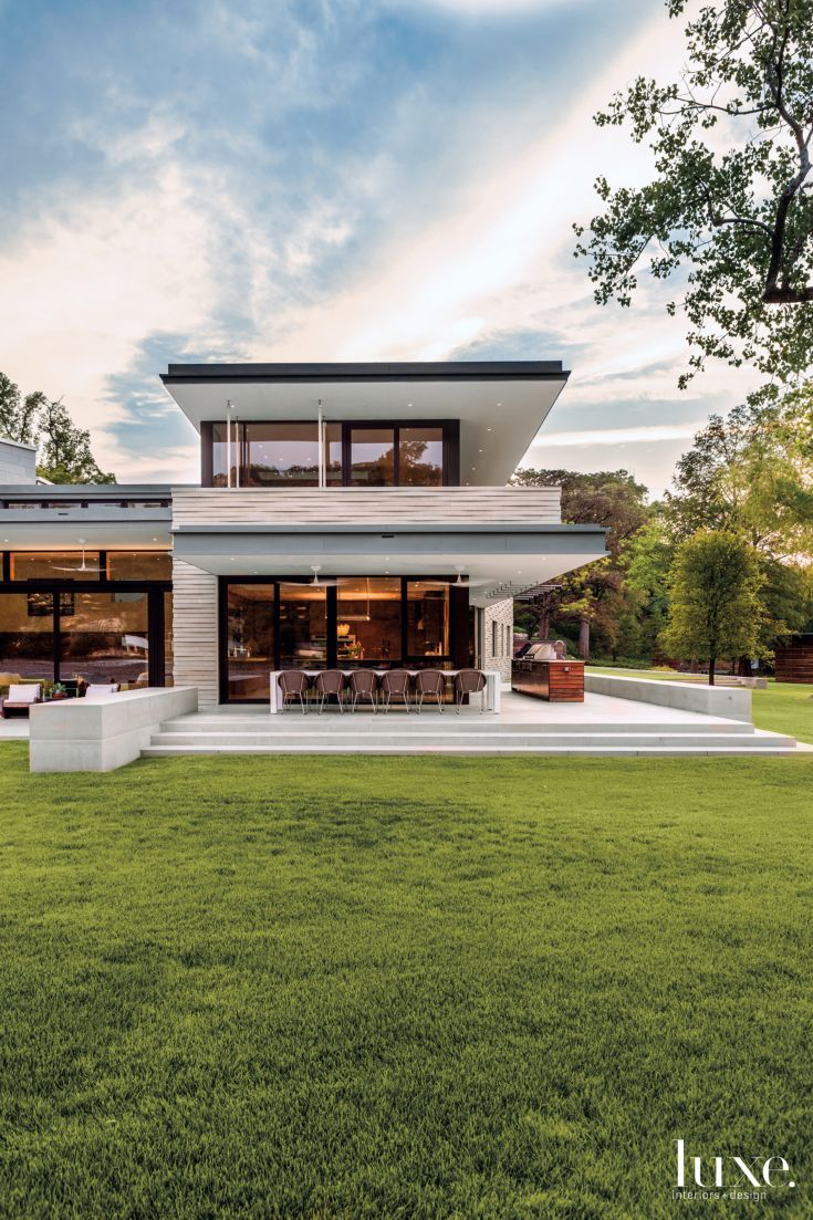 The architects clad the house in a custom-cut antique Lueders limestone veneer fabricated by A.J. Brauer Stone that evokes the ripples in the lake's surface. Vaughn Miller completed the outdoor dining room with a custom table from Weatherend Estate Furniture in Rockland, Maine, and Janus et Cie chairs. The landscape was installed by Tait Moring and Associates.