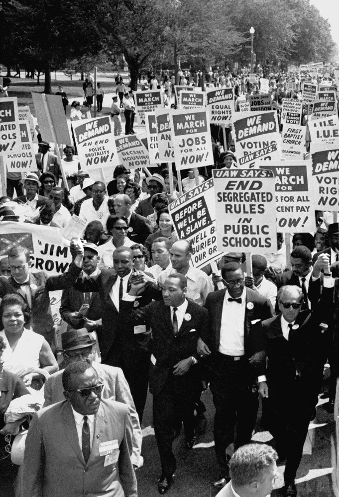 1963 March On Washington FILE - In this Aug. 28, 1963, file photo Dr. Martin Luther King, Jr., center front, marches for civil rights, arms linked in a line of men, in the March on Washington. It wasn't until the 1960s civil rights movement, exemplified by the historic march, that new laws began strengthening the federal role in civil right protection. Now, the Justice Department is expected to pursue civil rights prosecutions.