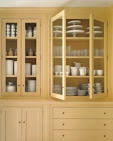 Yellow kitchen display cabinets with the glass door fronts...