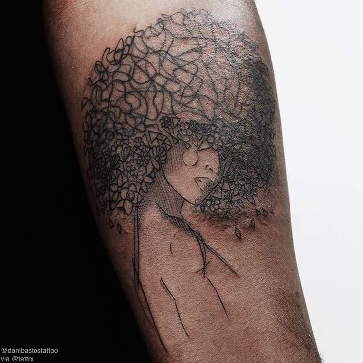 The afro, branches in the tree. Face perhaps a butterfly, the body, the trunk. Tree of life