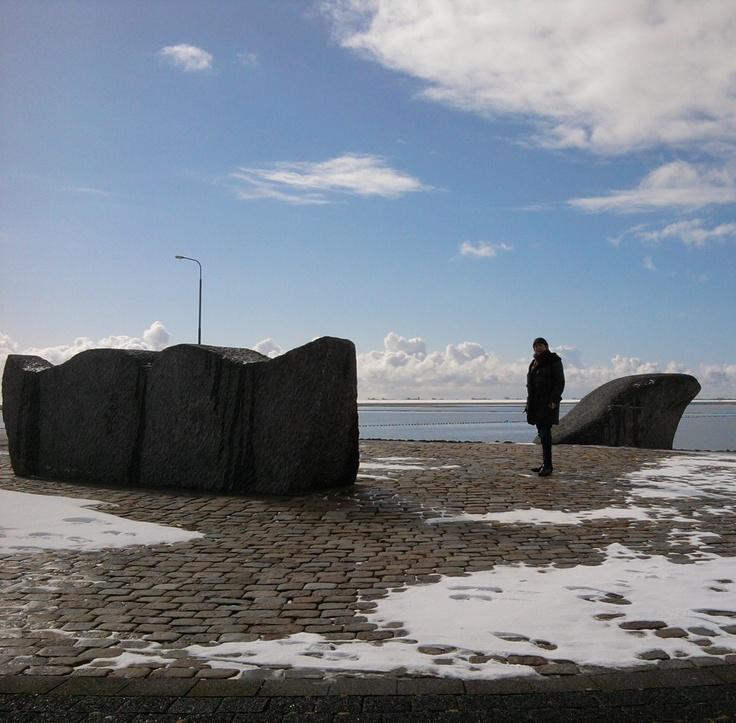 'Whale' 1993 by Anne Woudwijk.  Slope, Ferry-boat Terminal, Grândyk, Holwerd.          De walvis werd in 1993 in de Waddenzee, vlakbij de pier van Holwerd, onthuld. Na beschadiging door een aanvaring met de veerboot werden staart en snuit van Belgisch hardsteen uit het water gehaald. Het tweedelige beeld is in 2008 geplaatst op een talud voor de veerboot terminal. De zeepokken zijn er vanaf gekrabd. De breuk in de kop van de walvis- veroorzaakt door de aanvaring- is nog goed te zien…