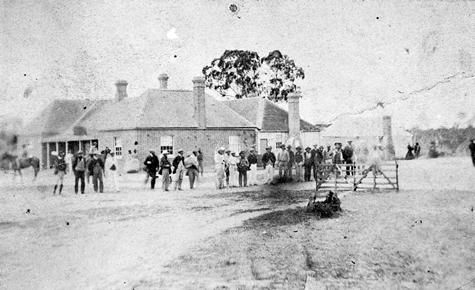 A group standing outside the 'Squatters Arms' inn. They are standing beside the last hurdle on a race track in 1865. This spot is now the central street intersection in Balmoral.
