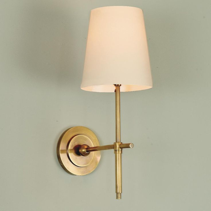 "Soho Sconce- 4 Finishes Soho Sconce: Incorporate urban style into your living space with this 1-light cast brass sconce. This minimalist piece comes with an ecru paper shade and is available in Antique Brass, Bronze, Antique Nickel or Polished Nickel. 60wt med base bulb. (15""Hx6""Wx9""D) This sconce is NOT lacquered so it will age gracefully with time."