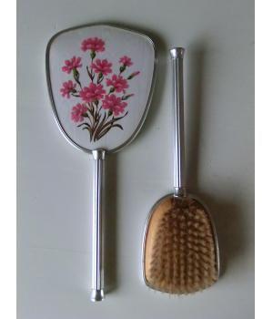 Kapset met bloemdesign uit de jaren `50 bestaande uit spiegel en borstel. Als je haar maar goed zit!Spiegel:Lengte 30,5 cmBreedte 12,5 cmDiepte 1 cmBorstel:Lengte 27 cmBreedte 8,5 cmDiepte 3,5 cm