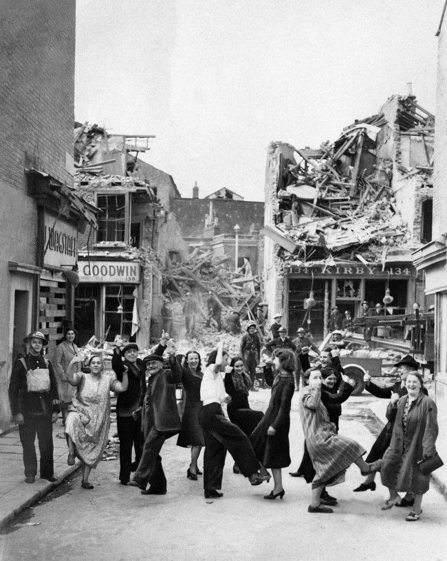 Residents of Lambeth Walk, S. London, doing the dance of the same name, 18/9/1940, by way of showing their spirits are still high despite bombs damaging the area.
