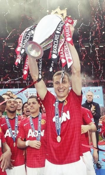 The captain lifts the trophy. Nemanja Vidic