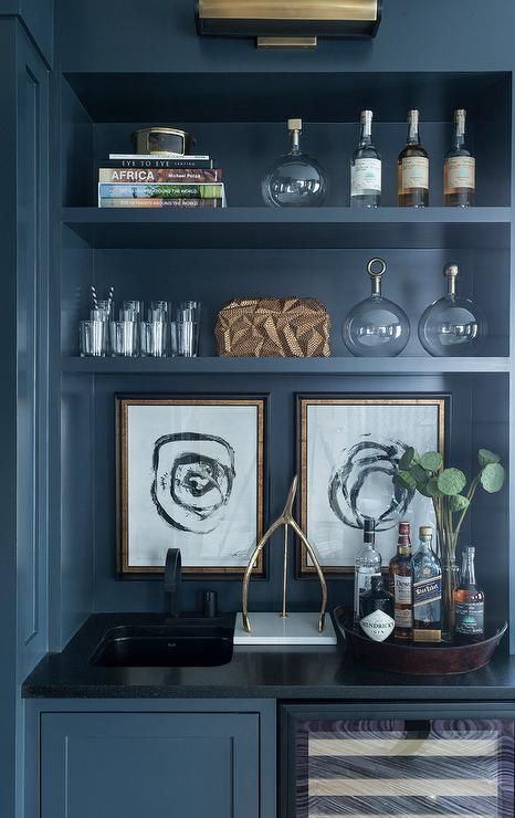 Blue den wet bar painted in Benjamin Moore Abyss features a blue cabinet fixed beside a glass front wine cooler positioned under a black quartz countertop finished with a black sink and matte black faucet.