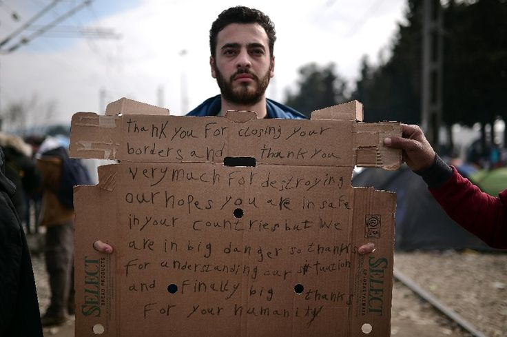 A man holds a sign in the makeshift camp at the Greek-Macedonian border, near the village of Idomeni, where thousands of refugees and migrants ar...