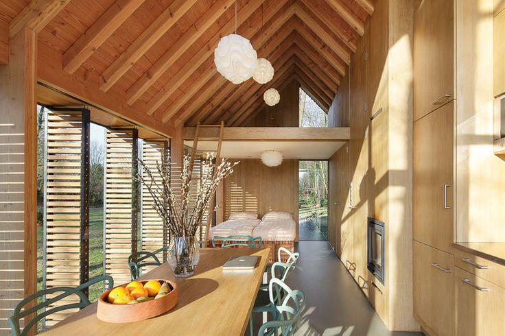 The house's open plan is neatly divided into public and private spaces, with the front containing the kitchen and living areas and the back holding the bedroom and bath, overhung by a small mezzanine. A hidden wooden panel can be drawn closed between the two sections for greater privacy