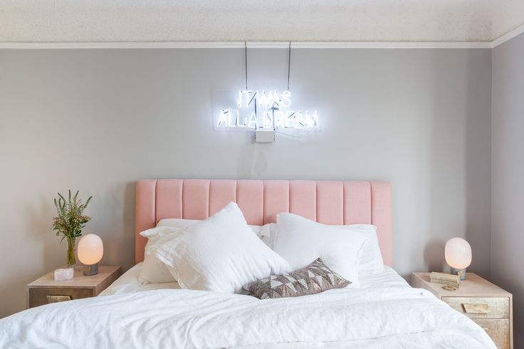 A perfectly feminine oasis. Complete with a custom neon side and blush pink headboard.