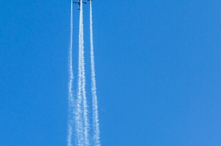 Airshow, Four Planes Flying Vertically With Long Smoke Streek.