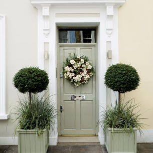 Sage green paneled front door. Traditional door surround. Lovely wreath. Symmetrically placed topiary planters.