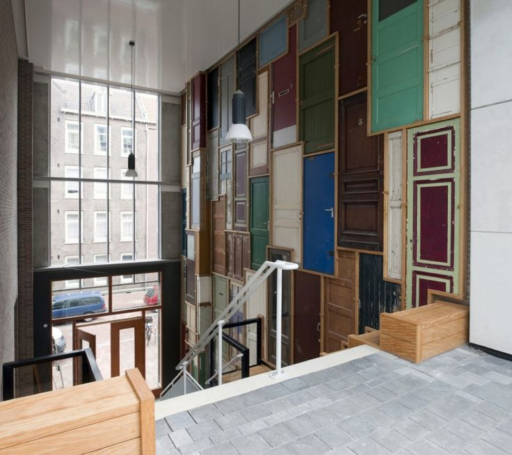 De Borneohof / Peter Geusebroek. Wall made from old doors before painting and walkways added.