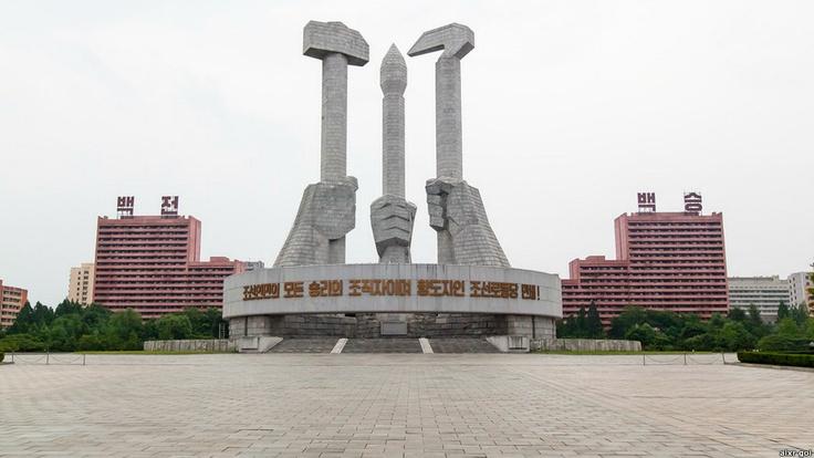 """""""Aqui vê-se um monumento ao Partido dos Trabalhadores da Coreia do Norte. O martelo e a foice simbolizam a união entre os agricultores e os trabalhadores. No meio do monumento há um pincel, o símbolo da elite intelectual""""."""