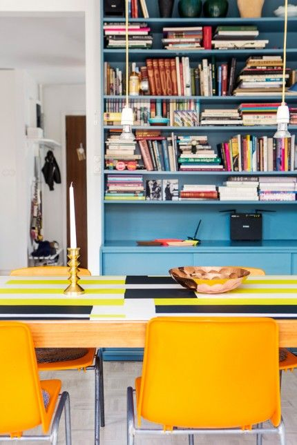 En platsbyggd bokhylla är målad i en mättad turkos färg som minner om gamla industrier från 50-talet. Bordets vaxduk, lampornas sladdar och loppisstolarna i gult utgör en pigg kontrast. Mässingsljusstakarna kommer från en loppis och skålen är av Tom Dixon.