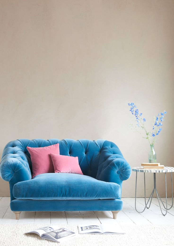 """Bagsie one of these!"" we all cried when we made the first one. Our very own version of the classic Chesterfield, this deep-buttoned beauty is one sumptuous, comfy love seat. Handmade in Britain and upholstered here in Teal Blue plush velvet - available in over 120 gorgeous fabrics."