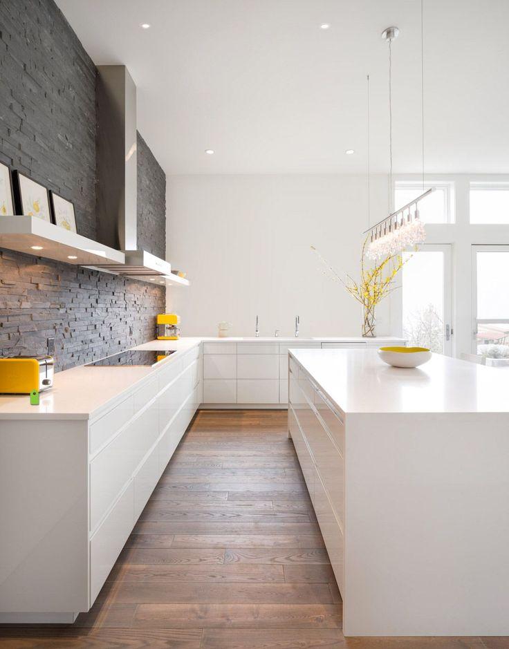 Cucina moderna con muro in mattoni scuri perfettamente abbinato ai mobili bianco lucido e al pavimento in legno massello