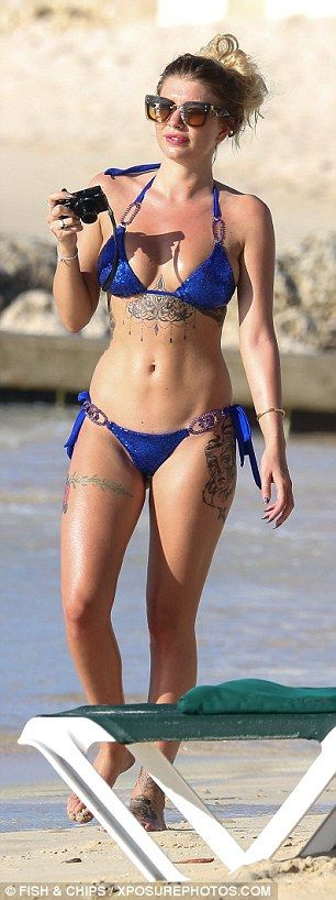 Lovely lady: She made the most of her amazing figure in a skimpy blue bikini, which showed off her generous assets and toned stomach