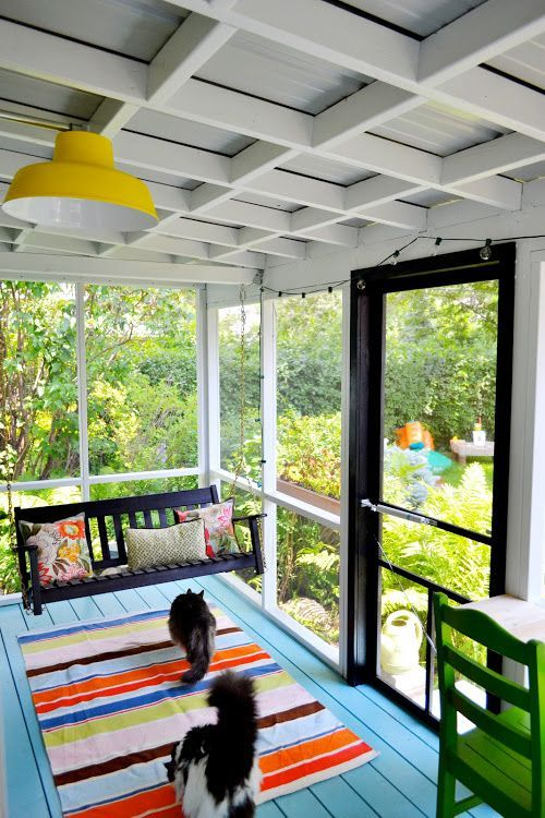 Bright and cheerful small screened-in porch with a blue painted floor.