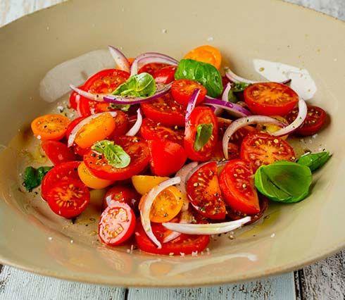 Tomatsalat med rødløk og basilikum smaker nydelig og er skikkelig sommermat. Se oppskrift her!